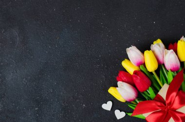 Bouquet of tulips and gift box on dark background. Greeting card for Valentine's Day, Woman's Day and Mother's Day.