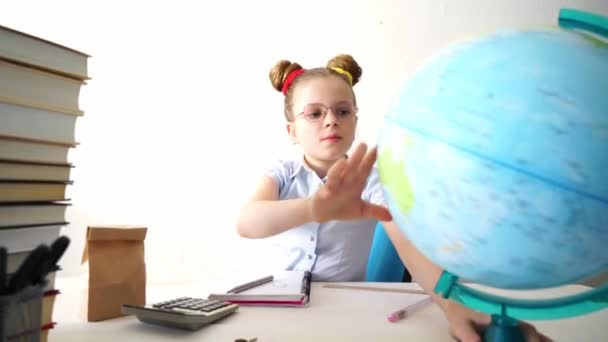 Back to school: girl schoolgirl sits at her desk and turns the globe with her hand. Homework.