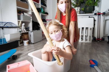 Stay home: Children in medical masks play with toys and ride in a white box. Family lifestyle portrait.