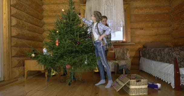Matka se dvěma dětmi obléká vánoční stromek na dovolenou. V interiéru vesnického domu, matka s dětmi, dívka a chlapec přátelsky vyndají vánoční hračky a pověsí je na zelený nadýchaný strom.