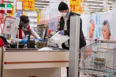 LUBIN, POLAND - 27 Mart 2020. Auchan süpermarketinin önündeki kasiyer ve yüzünde koronavirüs salgınından dolayı maske olan müşteri..