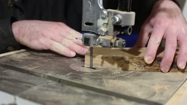 Ruce truhláře zpracovávají strom na pásové pily. Výroba dřevěných prken do kuchyně. výroba, obráběcí stroje v procesu. Recyklační stroje. Bez tváře.