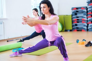 Fit women doing side lunges