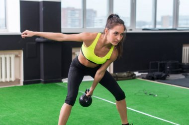 woman doing work-out swinging kettlebell
