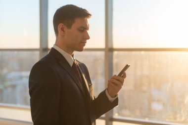 Man with smartphone in modern office