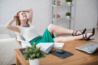 Businesswoman resting with hands behind her head