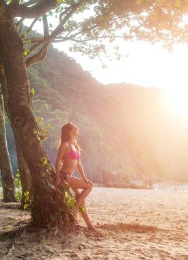 Attractive slim female tourist in bikini leaning against tree