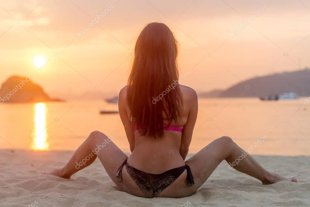 Back view of young female sitting on beach