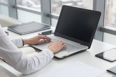 Businesswoman typing on laptop at workplace