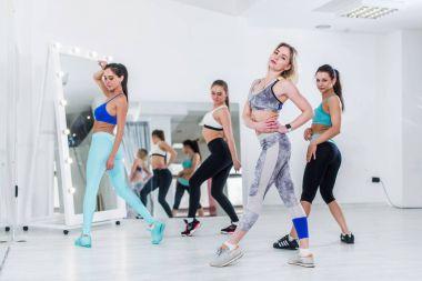 Female dance team wearing sports bra and leggings posing in studio standing backside and sideways turning to camera