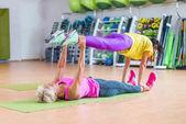 Fotografie Zwei weibliche Fitness-Modelle, die Yoga Übungen, einer liegend am Boden Matte halten Beine eines anderen über ihr im Sportzentrum