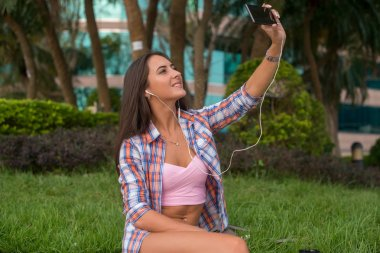 Happy young woman wearing headphones and taking a photo in the park sitting on the curb. Attractive female selfie.