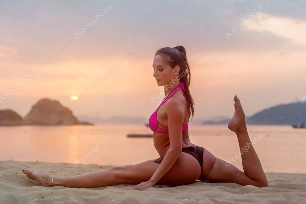 Photo in profile of slim fitness model with brown hair wearing bikini doing leg split exercise on beach at sunrise against sea, sky and mountains