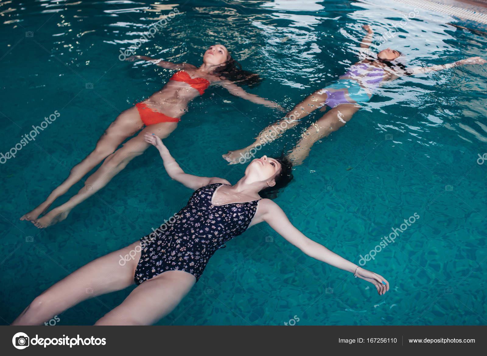 Junge schlanke Frauen beim Rückenschwimmen im Schwimmbad