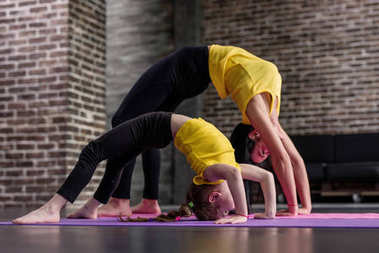 Young sporty mother and little girl doing stretching gymnastic exercises together standing in crab posture on mat in loft studio