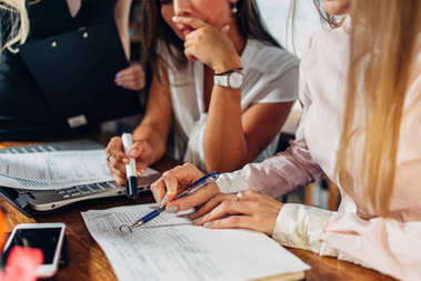 Close-up view of young women working on accounting paperwork checking and pointing at documents sitting at desk in office