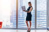 Podnikatelka drží notebook stojící v moderní kanceláři proti okno s výhledem na město