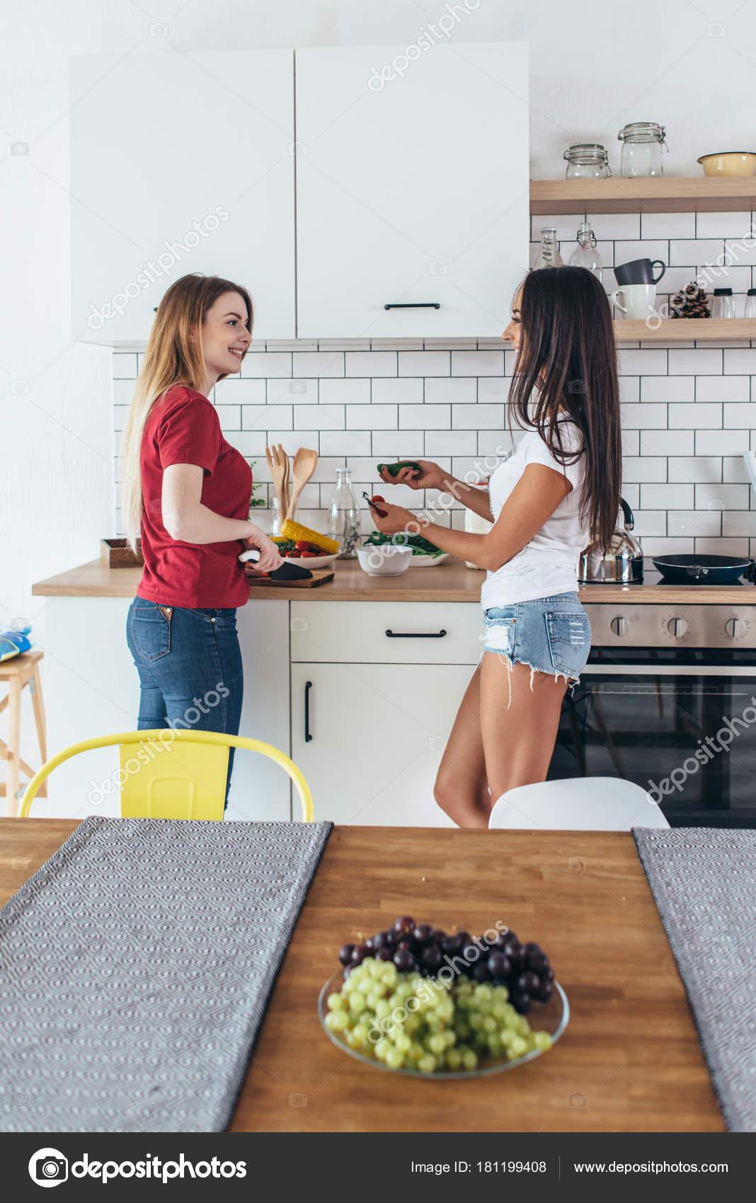 Dos mujeres en la cocina cocina hablando de preparación de