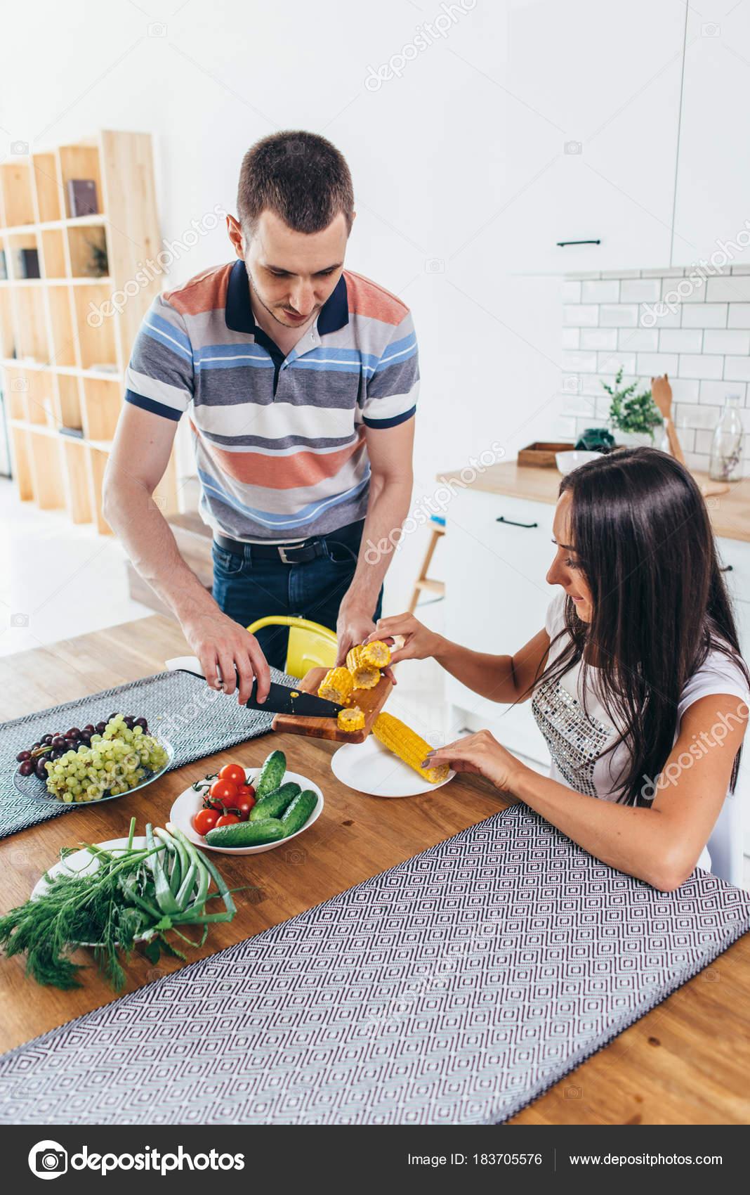 Frau am Küchentisch sitzen Essen Mais Gespräch mit Mann schneiden ...