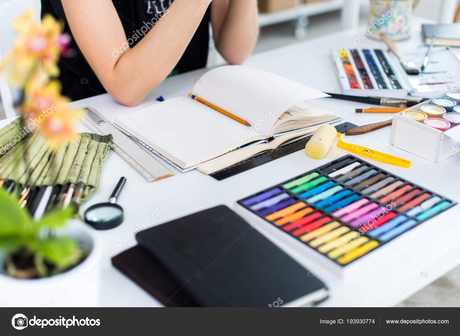 Close up angle view of a female painter drawing draft at sketchbook using pencil artist sketching in art studio with crayons set photo by