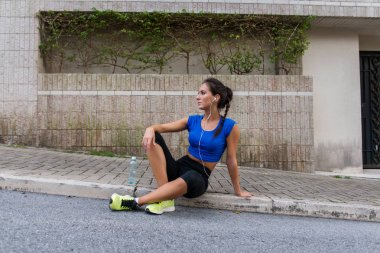 Young athletic female resting after running exercise, listening to music in earphones, holding a bottle of water, sitting on sidewalk city street.