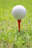 Golfový míček na dřevěné golf tee.