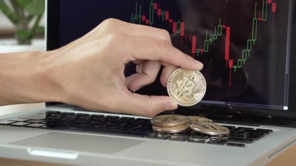 4k rozlišení muže, který si hraje s bitcoinovými mincemi a počítá je s grafem kryptoměny na notebooku