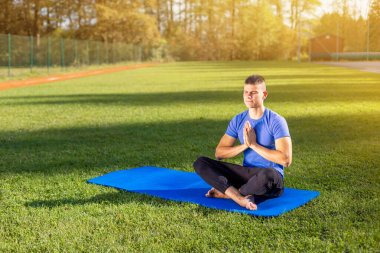 Man in park doing yoga