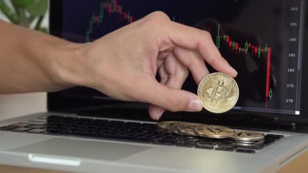 4k Auflösung eines Mannes, der mit Bitcoin-Coins spielt und sie mit Kryptowährungstabelle auf einem Laptop zählt