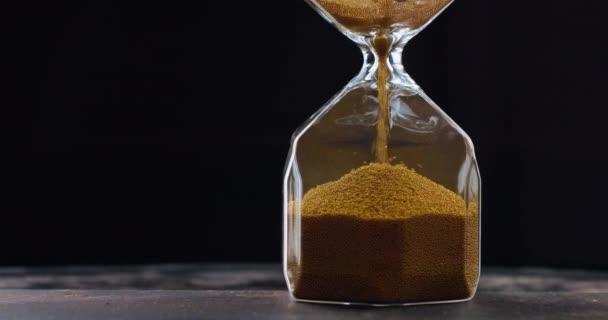 A homok a homokórában mozog. Óra zárása üveg óra. Régi klasszikus homokóra időzítő. A homok leesik és méri az időt.