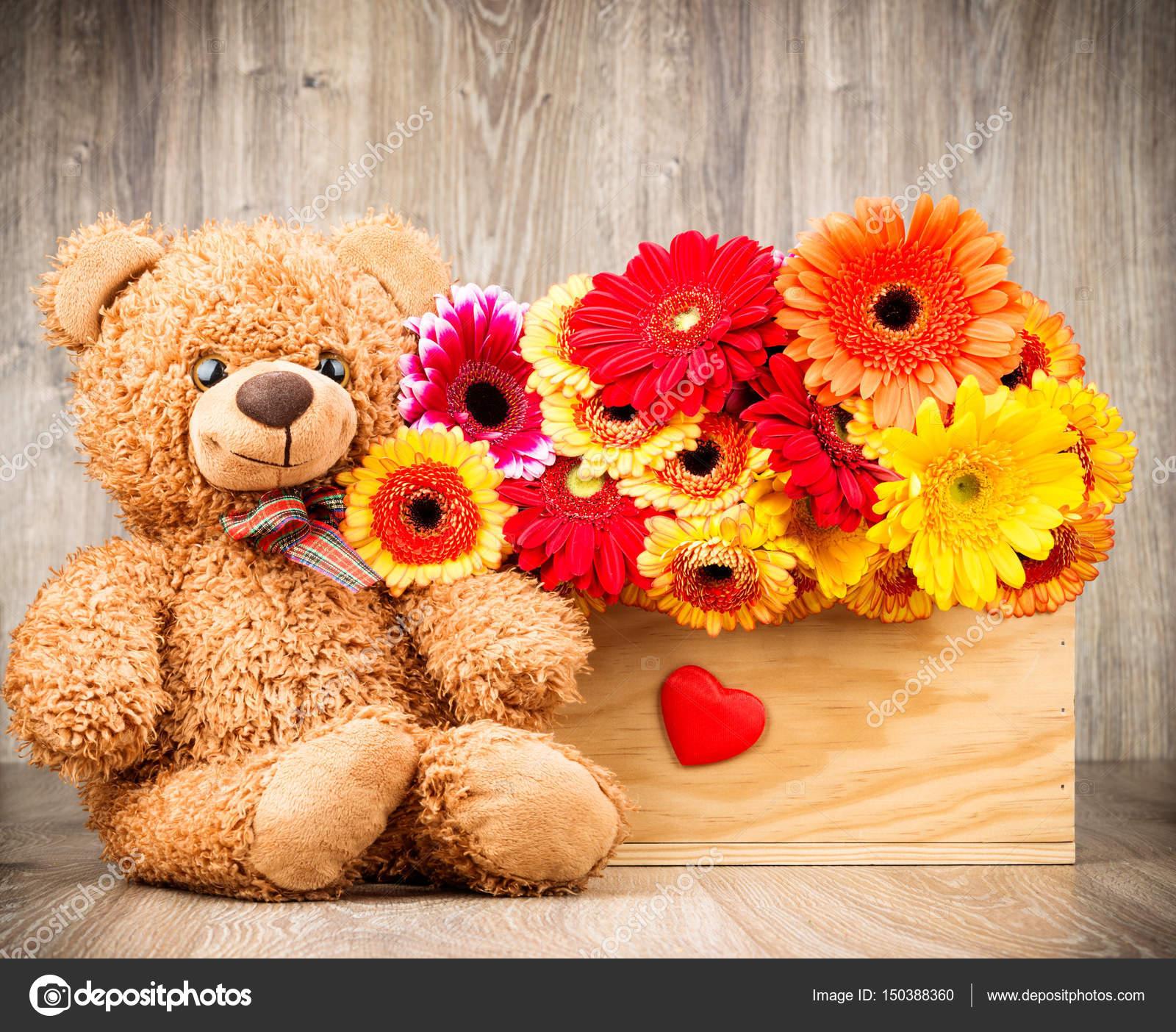 Flores e um ursinho de pelúcia em fundo de madeira — Fotografia de Stock d2befb644a4c8