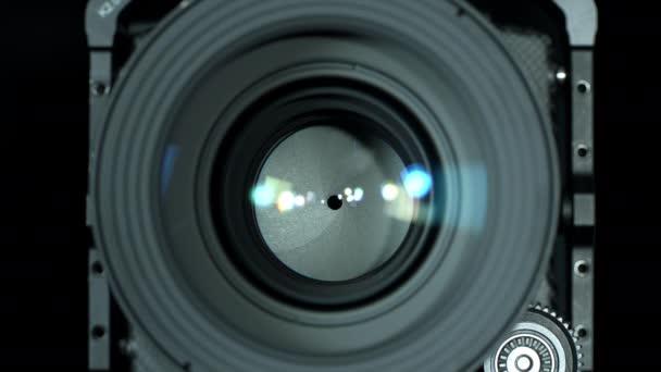 Profi fényképezőgép lencse rekeszének beállítása, közelkép. Nyitó és záró rekeszizom, elölnézetből. Fényképészeti koncepció. Szelektív fókusz sekély mélységű mezővel.