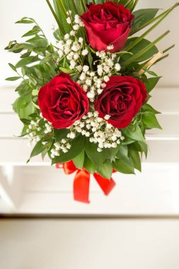 Closeup on a handmade red box with floral arrangement. The floral arrangement is three red roses and green leaves. A wonderful gift for a woman.