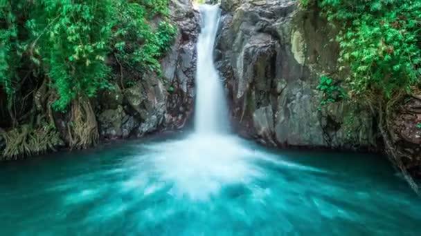 Timelapse tropické vodopád teče lesem husté džungle a spadá do divoký rybník v Bali, Indonésie