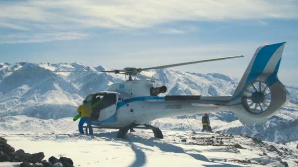 Lyžaři uvolnit lyže od přistál vrtulník v zimních horách