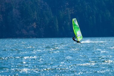 Lifestyle windsurfer on lake Alpnach in Switzerland during a windy spring day