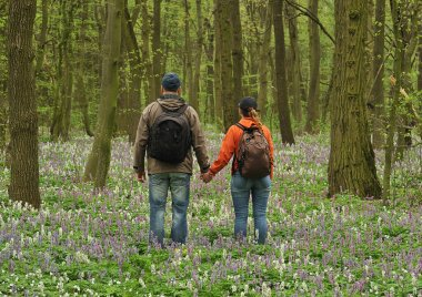 couple in the forest. man and woman in a flowering spring forest