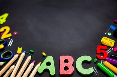 Multi-colored pencils and stationery on a black chalkboard