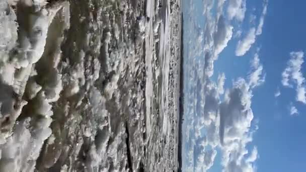 vertical timelapse of the river on which the ice melted, and the clouds in a blue sky run in the opposite direction