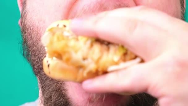 Tlustý muž s vousy jí burger detailní up
