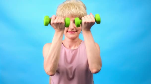 Dívka s legrační retro účes 70 dělá cvičení s malými činky na modrém pozadí.
