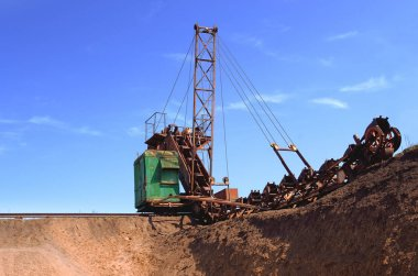 old bucket excavator of transverse dripping conducts the development of a quarry and extraction of clay
