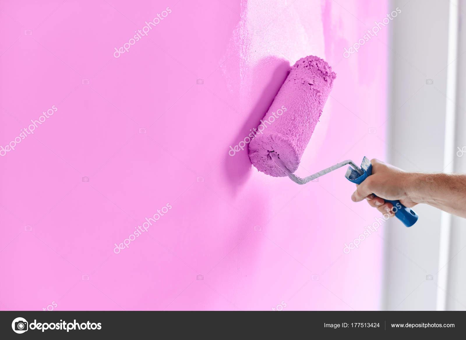 Couleur Lavande Peinture hommes de main peinture mur avec rouleau à peinture. appartement de