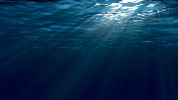 Tmavě modré moře povrch z pod vodou. Abstraktní vlny pod vodou a paprsky slunce svítí skrz