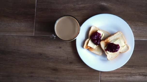 Cup of coffe with milk and two slices of toasted sandwich Bread with Butter and Raspberry Jam a white plate. Healthy breakfast with coffee. Free space for text. Side view.