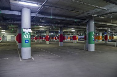 Moscow, Russia - April 22, 2020: Asphalt, dimly lit empty mall garage with ceiling lights.