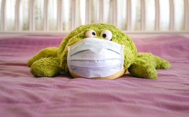 Green soft toy wearing medical face mask on top of bed. Work at home during quarantine concept.