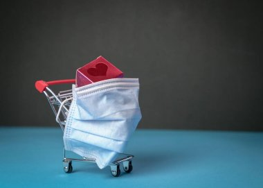 Shopping trolley or cart with love gift wrapped with medical face mask. Copy space.