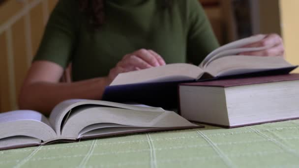 Žena otáčející stránky tlusté knihy a pak dát své brýle na čtení na vrcholu knihy.