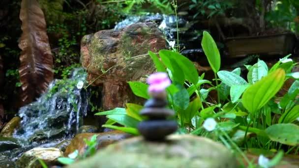 Oblázky naskládané do pyramidy s růžovým květem navrchu. Mini vodopád a skalní zahrada v pozadí. Zen, lázně, krása a wellness koncept